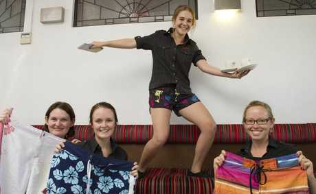 Metro Cafe staff (from left) Penny Freeman, Jaymee Wicks, Julia Ryan (surfing) and Henrietta Lee wear boardies at work to raise money for Surf Life Saving.