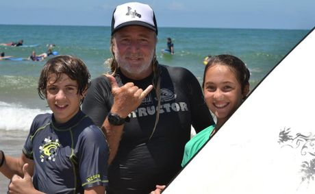 SUNNY DAY: Reef2Beach Surf School's Wayne 'Grom' Mellick with SUNfest kids Callum Dominguez and Matilda Moore at Agnes Water yesterday.