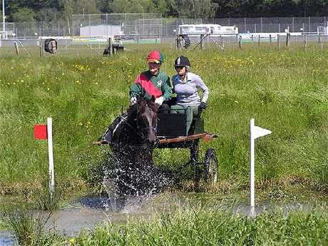 WET AND WILD: Ray Holdaway drives his horse Darkie through a water hazard at Clareville Showgrounds with groom Sally Barrett. PHOTOS/SUPPLIED