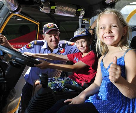 INSIGHT: Jake Robertson and Abbey Macgregor get a tour of the Ripley Rural Fire Brigade truck with John Bowles outside the Ipswich Art Gallery on Saturday.