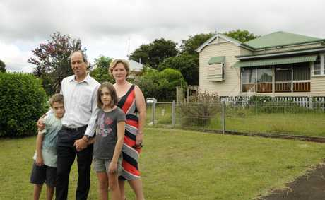 Joffre St residents Paul Herbert and Clare McConnel, with Paul's children Lawson and Selina Herbert in front of the house that is to be removed adn replaced by a two-storey building.