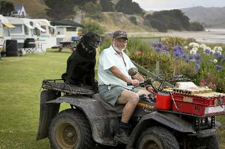 BETTER TOGETHER: Pourerere Beach Caravan Camp owner Dick Grenfell and his 7-year-old Labrador Charlie keep watch over the beach during the busy summer season.