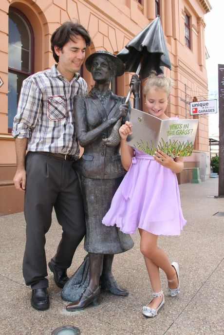 Young author Alyssa Mulholland shows her book to Fraser Coast councillor for community, cultural and family services George Seymour at the statue of Mary Poppins - a fictional character made famous by another Maryborough author P.L. Travers.
