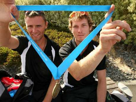 GOLDEN GLOW: Andrew Potter (left) and Thomas Jenkins hold up a gold medal at Hawke's Bay Airport yesterday.