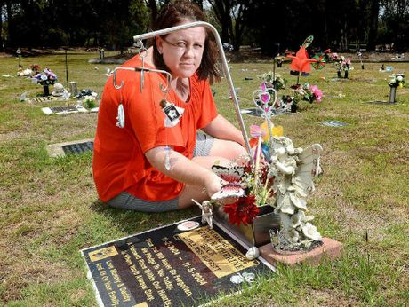 SHATTERED: Mary Beck at her daughters grave at Warrill Park Lawn Cemetery. Mary is upset that the cemetery staff have placed letters on graves asking for all trinkets to be removed.