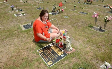 Mary Beck at her daughter's grave at Warrill Park Cemetery. Mary is upset that the cemetery management have placed letters on graves asking for all trinkets to be removed from graves.