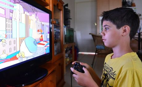 Caleb Amatto playing one of his favourite games, a QUT report says that children could be better off playing video games over watching television.