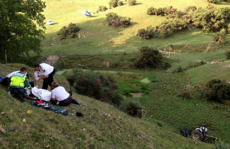 ON-SITE CARE: St John paramedics attend to a 70-year-old farmer, seriously injured when his tractor rolled down this steep hillside in the Turakina Valley on Tuesday. PHOTO/SUPPLIED