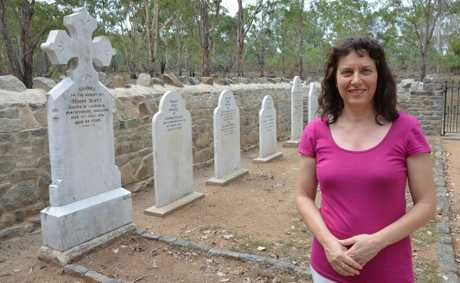 RESTORED: Jenny Thomas stands in front of the grave of her great, great, great grandfather Simon Scott whose grave was restored following the 2011 floods.