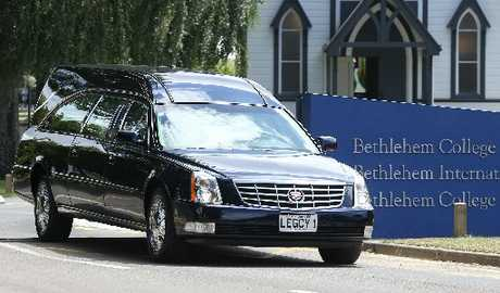 A hearse carries the body of Caitlin Dickson away from her funeral.