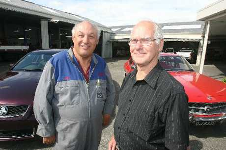 LONG ROAD: Ernie Theedom (left) and Stan Smith, with two cars that span the years of their time with Waggs, the Holden of today and a Kingswood first plated in 1972.