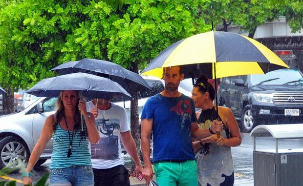 Plenty of brolleys in Hastings Street at Noosa as cyclonic conditions arrive on the Coast. Photo Geoff Potter / Noosa News.