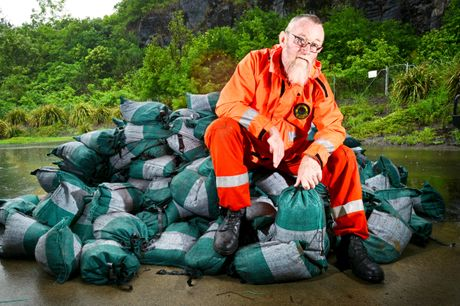 Graeme Hall of The Lismore SES sitting on a pile of sandbags at the Lismore SES depot. Photo Patrick Gorbunovs / The Northern Star