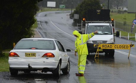 An RTA worker turns around cars at South Grafton as the Pacific Highway is cut north and south of Grafton by rising floodwaters.