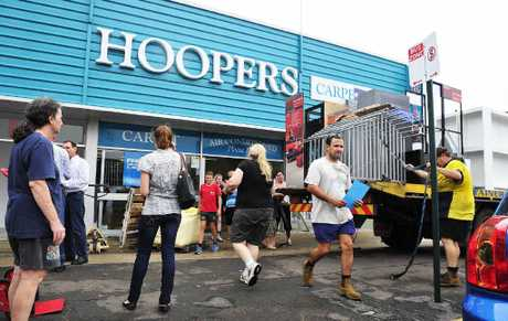CHIPPING IN: A team of volunteers helped clear Hoopers Carpet One before flood waters entered yesterday.