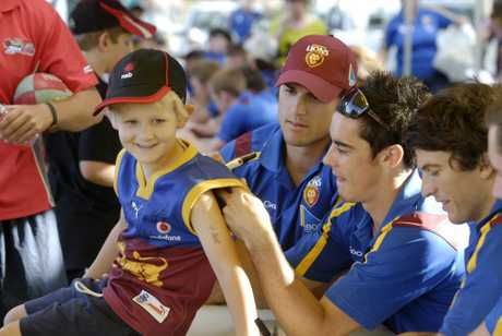 Jack Rattray has his jersey signed by (from left) Jamie Charman, Jesse O'Brien and Rohan Bewick when the Brisbane Lions last visited Toowoomba in 2011.