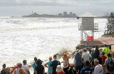 Onlookers watch as the Mooloolaba lifesaving tower is stands on dangerous ground.