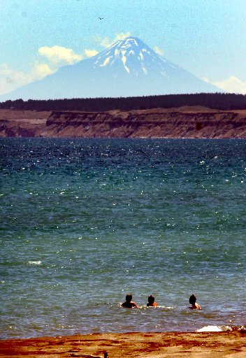 COOLING OFF: Mt Taranaki provides a striking backdrop to a group of swimmers at Castlecliff beach yesterday, as the warm summer weather continues. PICTURE/STUART MUNRO
