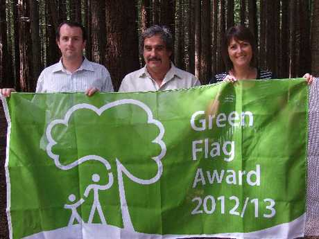 Rotorua District Council staff (from left) Joby Barham, Garry Page and Julianne Wilkinson with the Green Flag Award for the Redwood Forest. Photo / Supplied