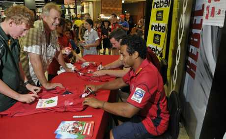 Scott Tiran (left) and Michael Weston join the queque at Rebel Sport Grand Central today to have merchandise autrographed by Queensland Red players David MdDuling (left) and Will Genia.