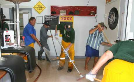 Rural firefighters from Cawarral and The Caves lend a hand to clean up the Bajool Hotel after flash flooding ripped throught the small time south of Rockhampton last Friday as ex Cyclone Oswald dumped heavy rain across Central Queensland. Photo: Chris Ison / The Morning Bulletin