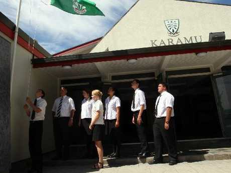 Karamu High School principal Martin O'Grady (second from left) and a group of students look on as Reuben Cash lowers the school flag to half mast out of respect for Karamu old boy and veteran broadcaster Sir Paul Holmes, who passed away early yesterday morning.
