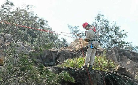 REGENERATION: Mark Beaton, from Austspray Environmental, abseiling at Black Head in a bush regeneration project.