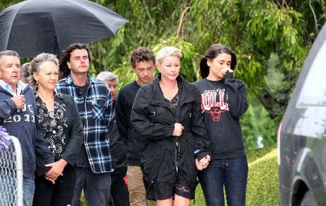 Sir Paul Holmes' brother Ken Holmes (far left), son Reuben (in checked shirt), wife Lady Deborah and daughter Millie Elder Holmes watch as his hearse leaves Mana Lodge for Auckland yesterday morning. Photo / Paul Taylor