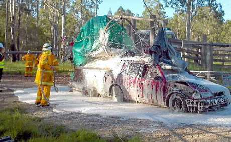 FOAMING WITH RAGE: The 'Mad Max' car blocking the gate at Glenugie gets a precautionary foaming from the RFS.