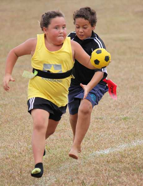 BLAZE OF COLOUR: Flying Ngapuhi junior Erina Perese (in yellow) looks to shake off the determined chasing of KAI player Seven Ngawati