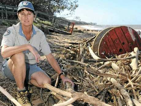 STORM DEBRIS: Ranger Lisa Emmert inspects the mess left at Mon Repos Beach by wild weather and flooding.