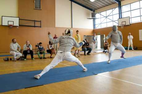 EN GARDE: Anjan Banerjee (left) and Bryan Clark begin a fencing bout. PHOTOS/RAE CLIFFE