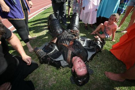 SPENT FORCE: Charlie Tapsell lies exhausted after completing a 5km run around the Tauranga Domain track in a full suit of authentic medieval armour weighing 40kg in 25°C heat.