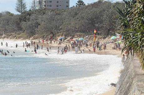 Waves are lapping against the retaining walls at Mooloolaba Beach at high tide after sand loss from recent big seas.