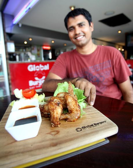 Arpit Jani with a serving of chicken wings at Global Burgers. Photo Allan Reinikka / The Morning Bulletin