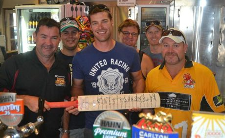Jimmy Maher presents a signed bat to Souths captain Scott Hilton at the Comm Hotel on Saturday while teammates look on.