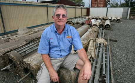 An Aussie Man's Shed owner Brien Jacob sits among flood-damaged stock at his Gladstone Rd business which was flooded again this year.