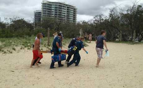 The kayaker is carried across the beach to an ambulance.