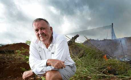 NO OPTION: Bangalow farmer Ray Hick kneels next to his burning fruit trees that he is destroying after the Federal Govt introduced a ban on chemicals to control fruit fly.