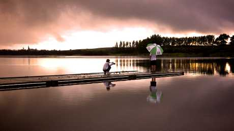 Jacqui Dick took this shot of her son Daniel Cooper taking photos of her husband Ron at Lake Ngaroto. She says the light was amazing between showers as the storm approached
