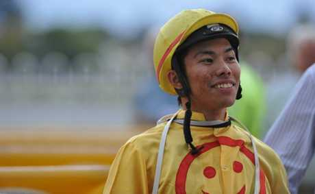 Jockey Allan Chau is all smiles after winning race 6, the Tooheys Old Handicap, on Tuesday. Photo: JoJo Newby/The Daily Examiner