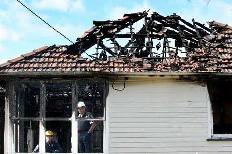 DESTROYED: Police examine the Anzac Parade house that was gutted by a fierce fire on Saturday. PHOTO/BEVAN CONLEY