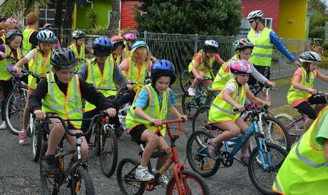 With bike helmets and high visibility vests on, students from Kaponga Primary School are safely equipped for a ride on the open roads.
