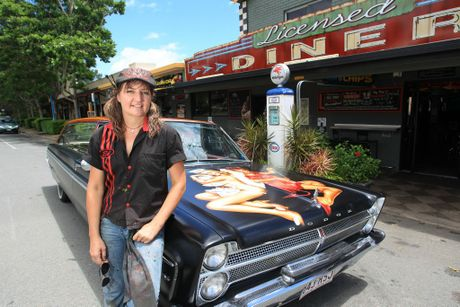 Vick Pattison with her 1965 Dodge Phoenix hearse,  in front of Rick's Garage in Palmwoods.