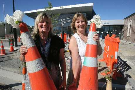 BEAUTY: Carterton District Council officers Jeanine Gribbin and Lorraine Gittings with the road cones decorated with flowers outside the Carterton Events Centre in Holloway St. 