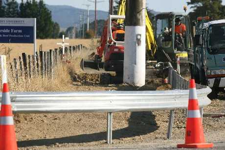 BARRIER: Contractors install a $30,000 guard rail about a power pole at the corner of Miki Miki Rd and SH2, where a young mother was killed in a car crash in 2011.