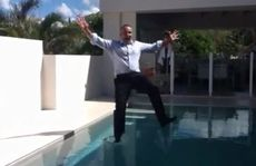 Auctioneer Justin Marsden jumps in the pool fully clothed after selling a Sunshine Beach house.