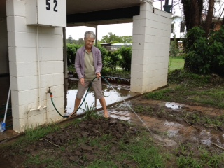 A Brushgrove resident tries to hose out her property after all the rain yesterday.