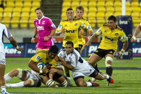 MILESTONE NIGHT: Victor Vito is brought down by Luke Braid and Piri Weepu, playing his 100th Super Rugby match, during the Hurricanes and Blues game on Saturday.