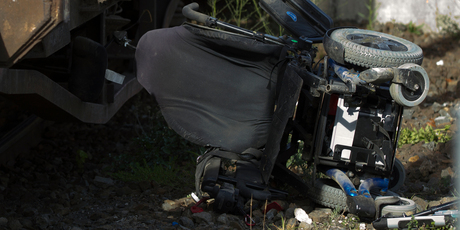 A wrecked wheelchair sits near a train by Morningside station in Auckland this morning.
